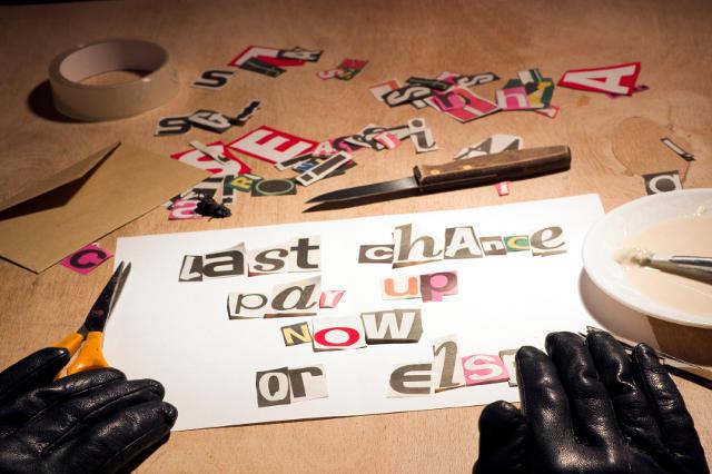Drohbrief aus ausgeschnittenen Buchstaben und schwarzen Handschuhen des Verfassers