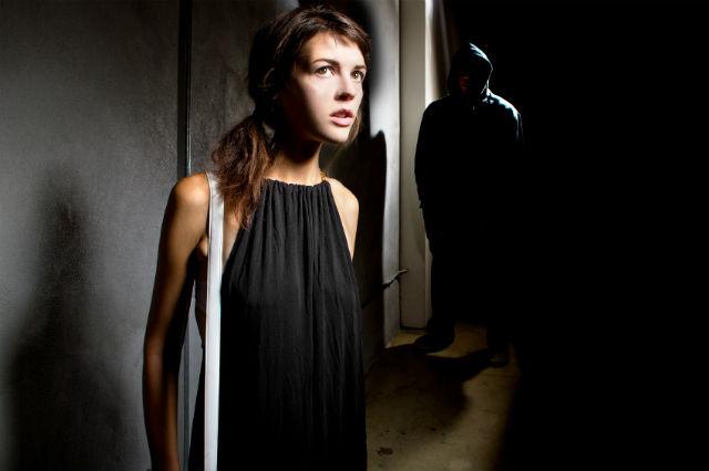 Frau in dunklem Raum im Schatten eine auflauernde Person