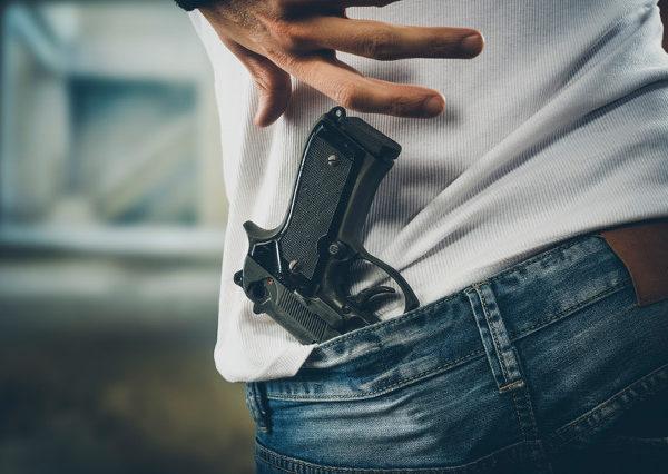 Man grabbing quickly a pistol, hands close up