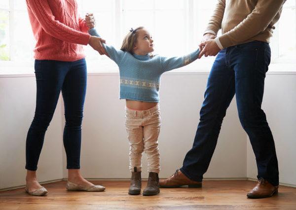 Elternziehen an den Armen von einem Kind in unterschiedliche Richtungen