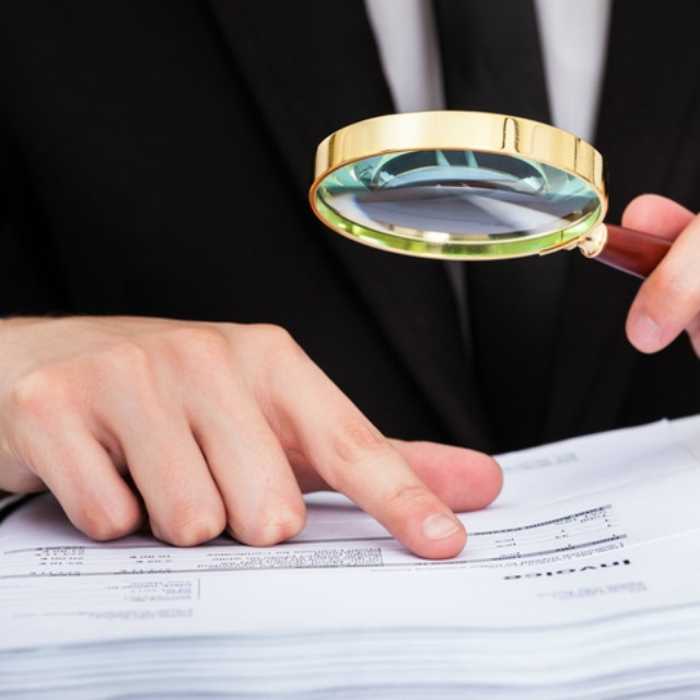 Mann untersucht Kostendokument mit einer Lupe