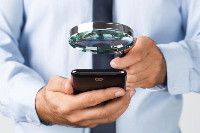 Ein Mann untersucht sein Handy mit einer Lupe