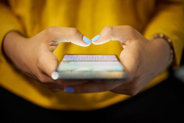 Eine junge Frau tippt eine Nachricht auf ihrem Smartphone
