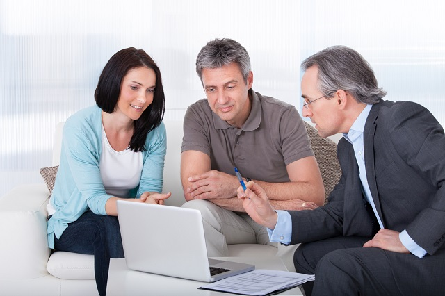 Paar beim Bankberater vorm Laptop sitzend