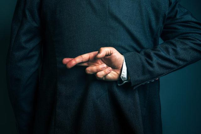 Geschäftsmann kreuzt die finger hinter seinem Rücken