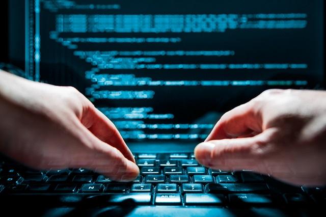 Hände tippen verschlüsselte Daten auf Laptop