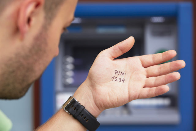 Mann guckt am Bankautomaten die Kontopin von seiner Hand ab.