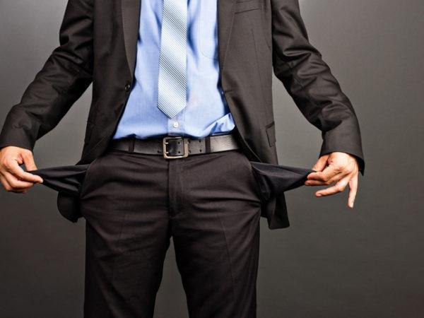 Ein Geschäftsmann stülpt die leeren Hosentaschen seines Anzugs auf links