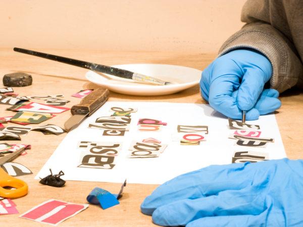 Ein Mann mit Handschuhen erstellt einen Erpresserbrief mit ausgeschnittenen Buchstaben aus der Zeitung