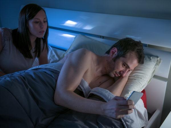 Eine Frau beobachtet ihren Freund beim heimlichen schreiben von SMS im Bett