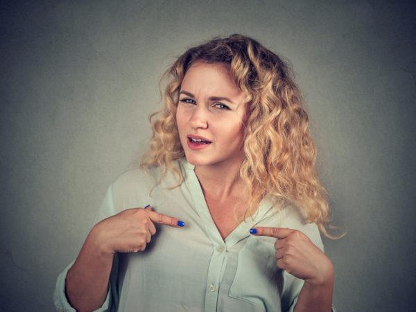 Junge Frau zeigt ungläubig auf sich selbst