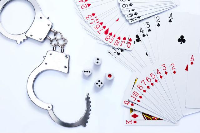 Handschellen, die neben einem Kartenspiel und Wuerfeln auf einem Tisch liegen