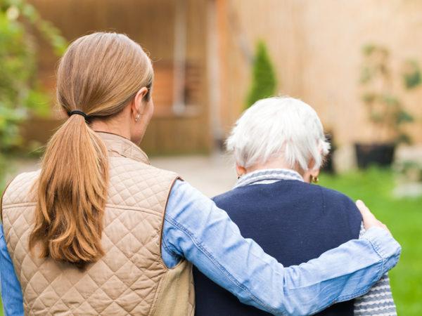 Frau begleitet ältere Dame beim Gehen